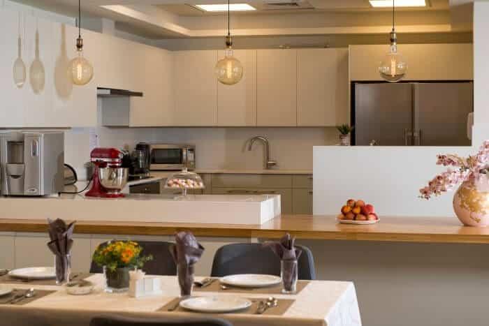 במרכז הבית ניצב המטבח הפתוח וחדר אוכל עם שולחן מרכזי לארוחות משותפות